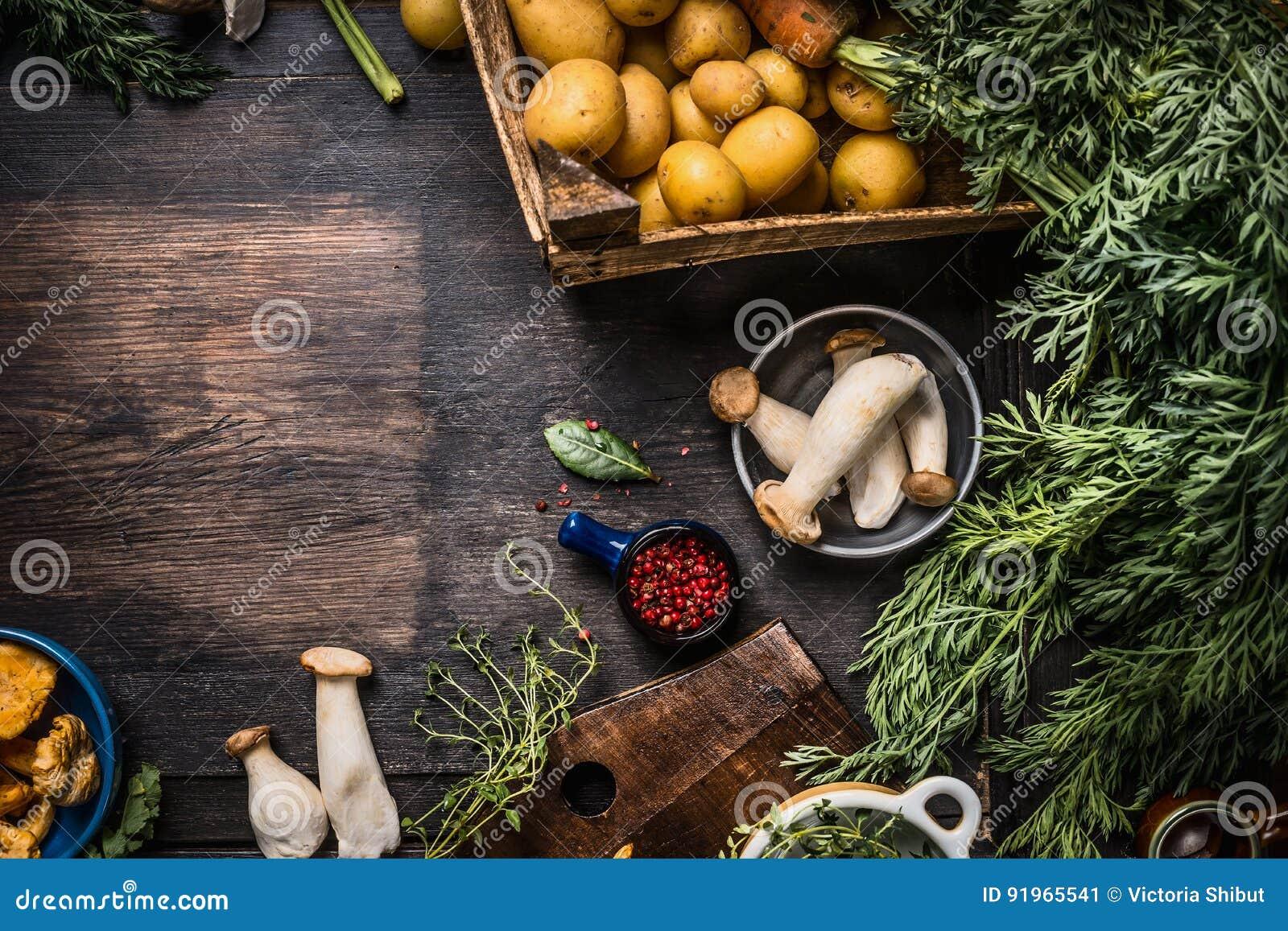 Säsongsbetonade matlagningingredienser för höst med skördgrönsaker, gräsplaner, potatisar och champinjoner på mörk lantlig köksbo