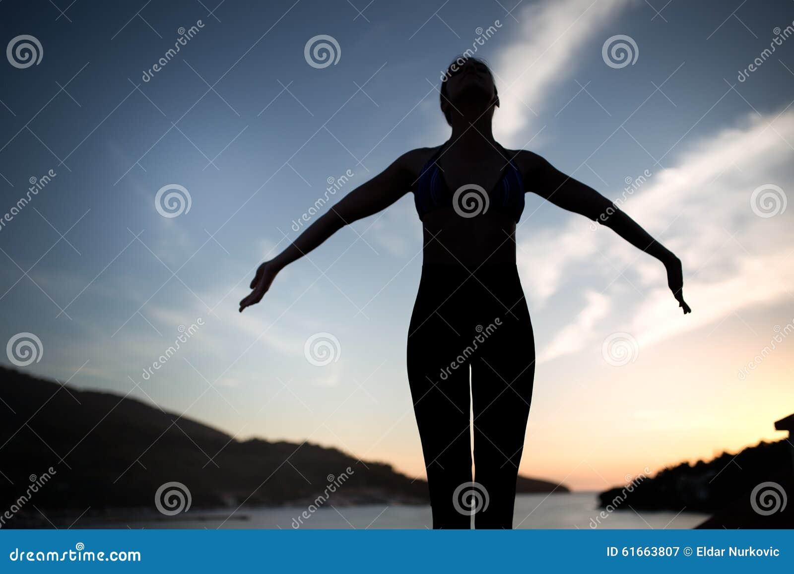 Sätta på land det carefree begreppet som dansar den sunda strömförande kvinnan för solnedgångsemestervitaliteten sunt bosatt be