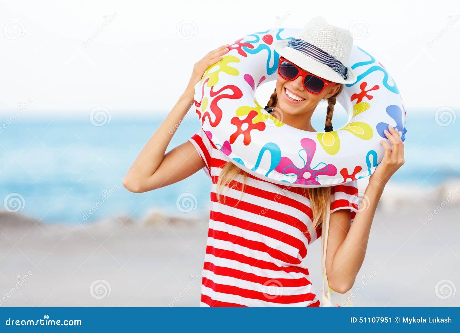 Sätta på land lycklig och färgrik bärande solglasögon för kvinnan och strandhatten som har sommargyckel under loppferiesemester