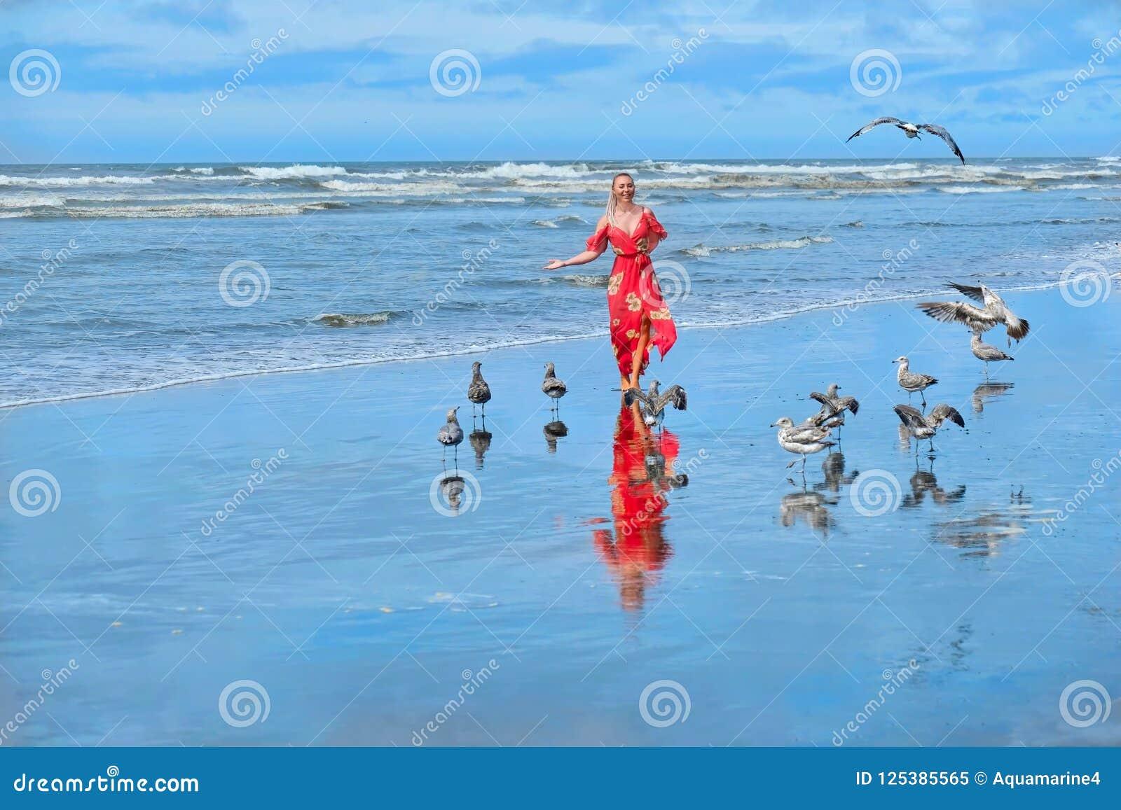 Sätta på land semestern Kvinnaspring på stranden vid havet med seagulls