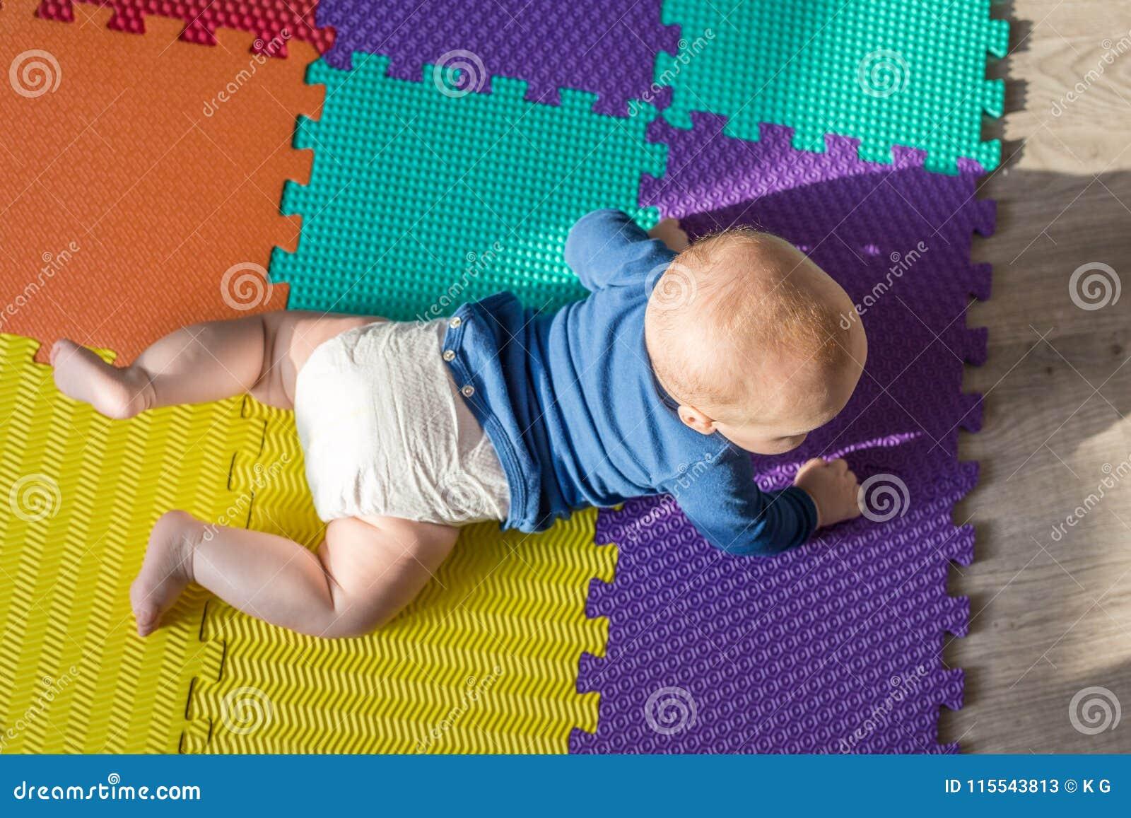 Säuglingsbaby, das auf bunter weicher Matte spielt Das kleine Kind, das zuerst kriechen macht, tritt auf Boden Draufsicht von obe