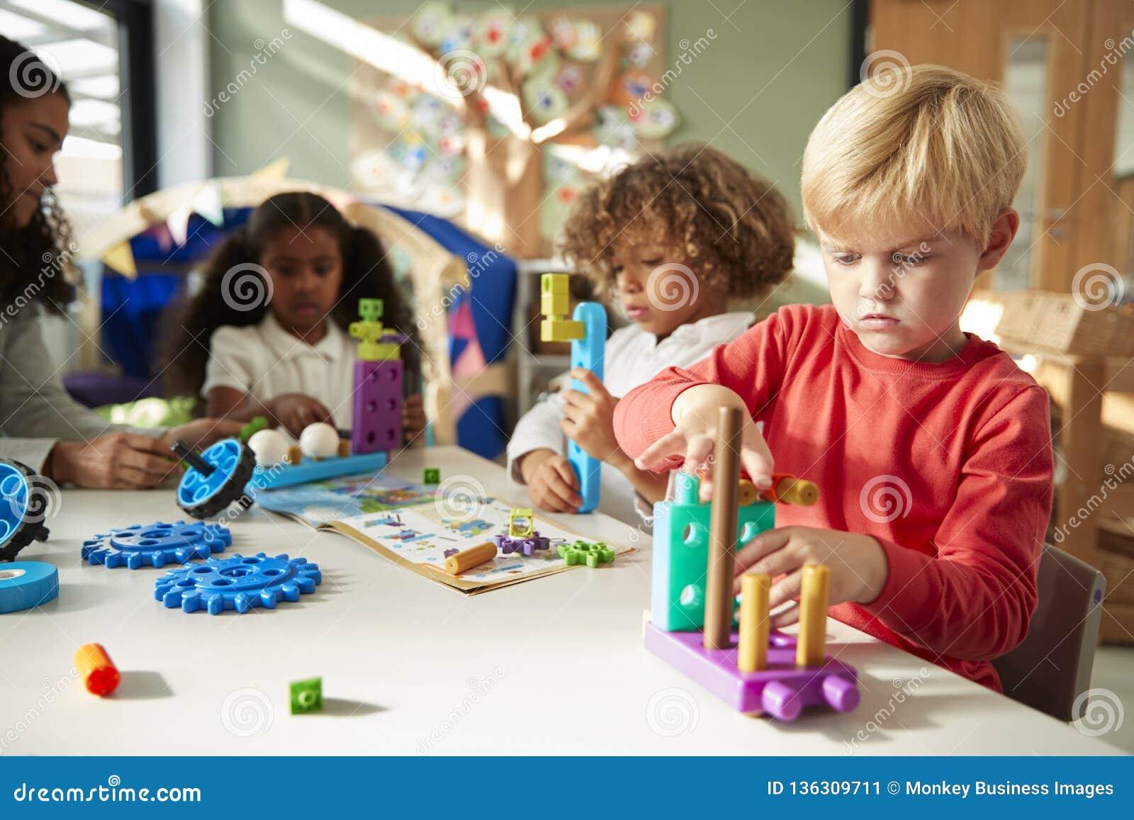 Säuglingsschuljunge, der an einem Tisch unter Verwendung der pädagogischen Bauspielwaren mit seinen Mitschülern, Abschluss oben s