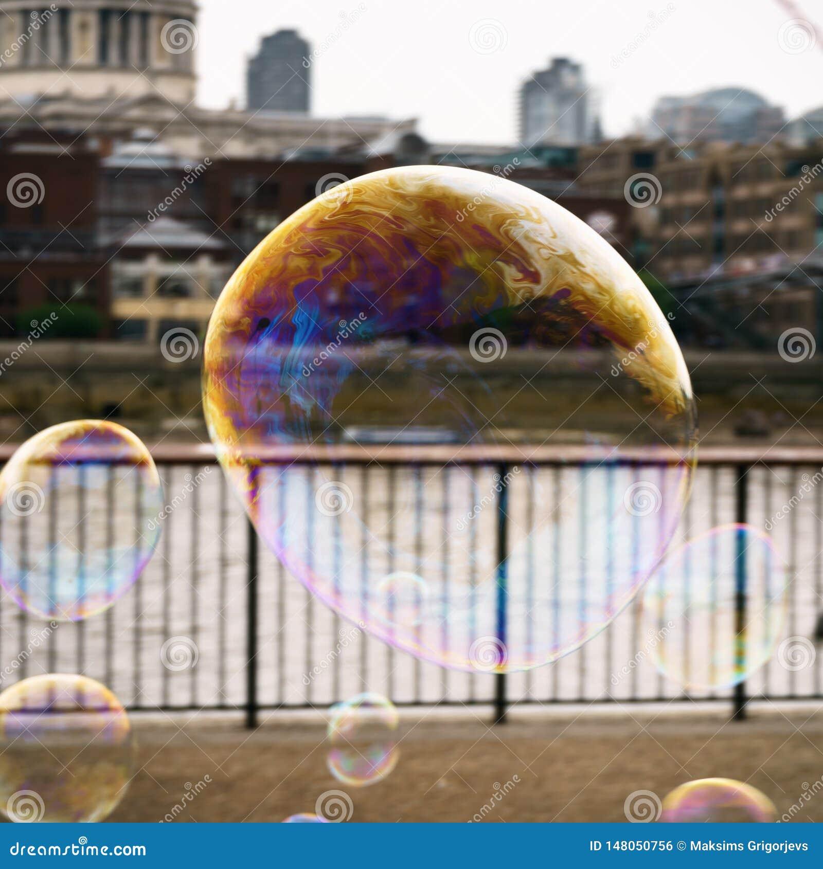 Såpbubbla med reflexionen av byggnader i London med sikt på flodThemsen