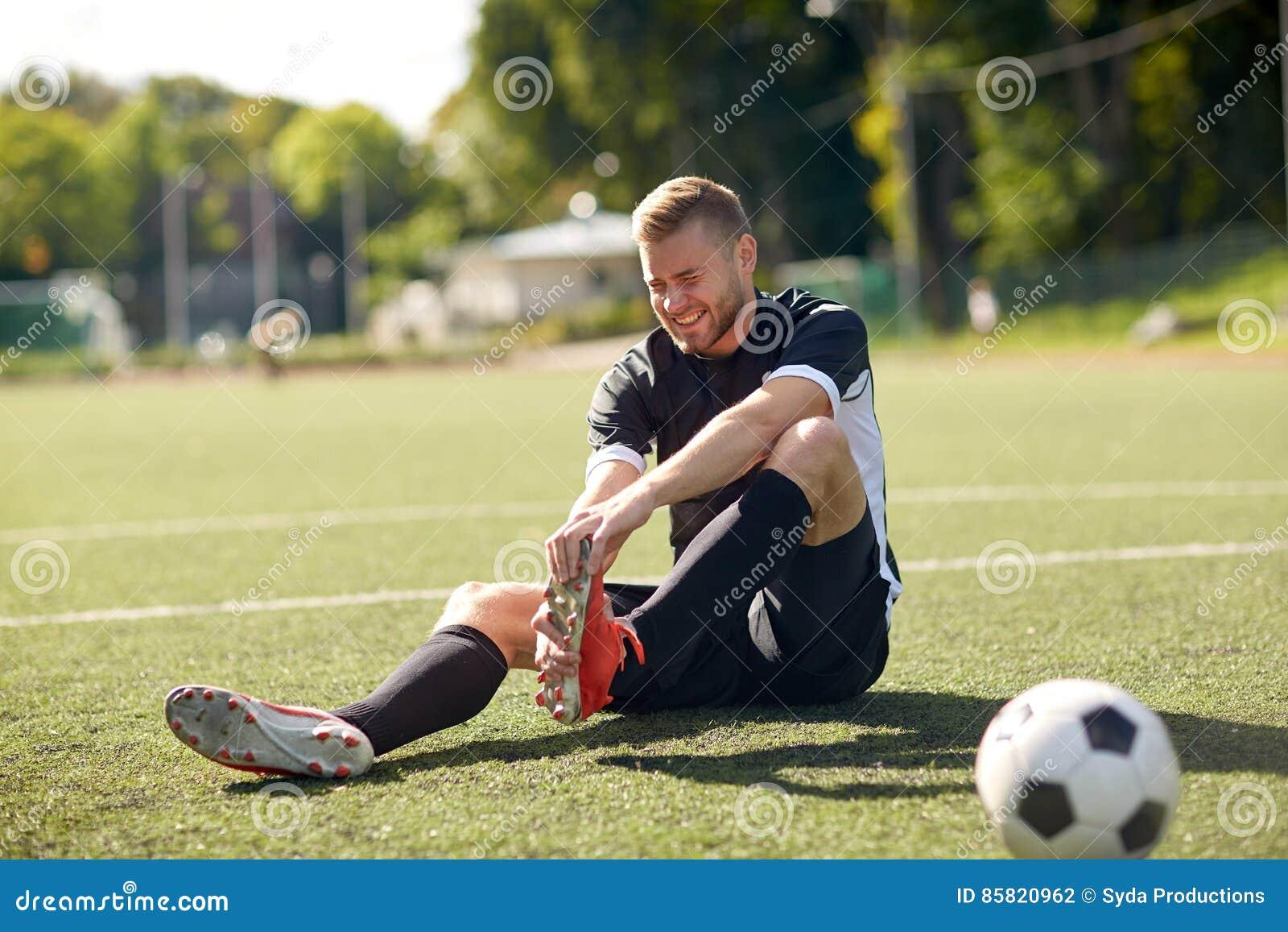 Sårad fotbollspelare med bollen på fotbollfält