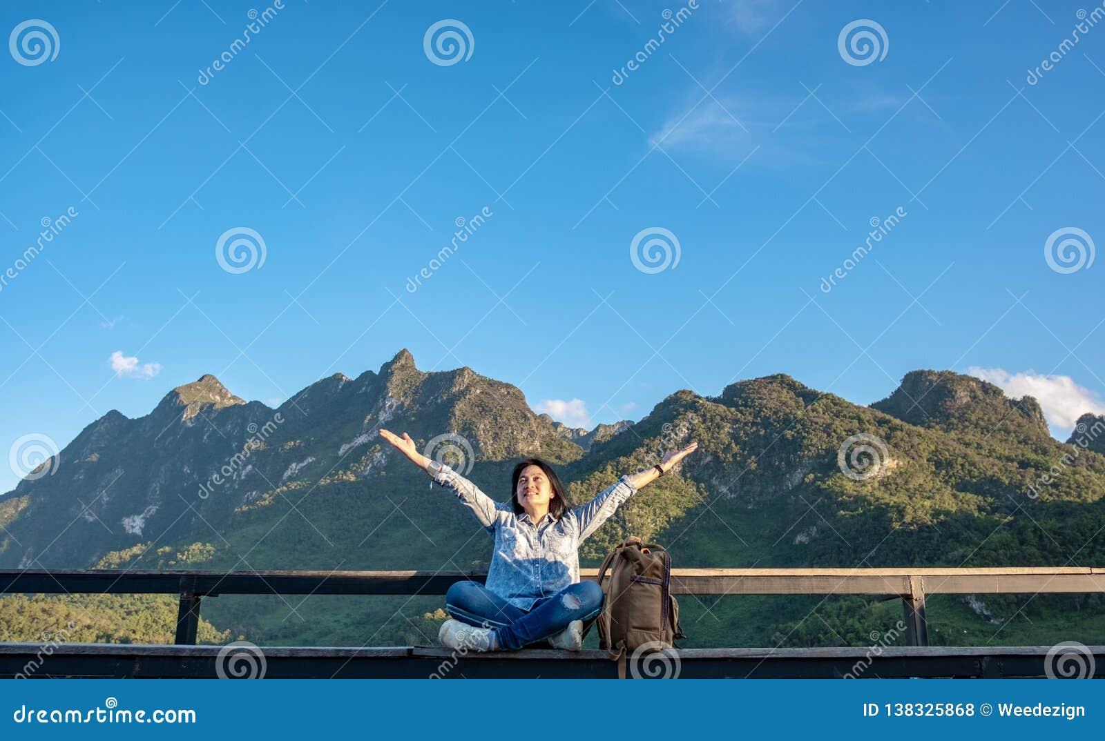 Séance asiatique et bras de voyageuse de femme dans le ciel à la terrasse de point de vue à la vue de paysage de la montagne avec