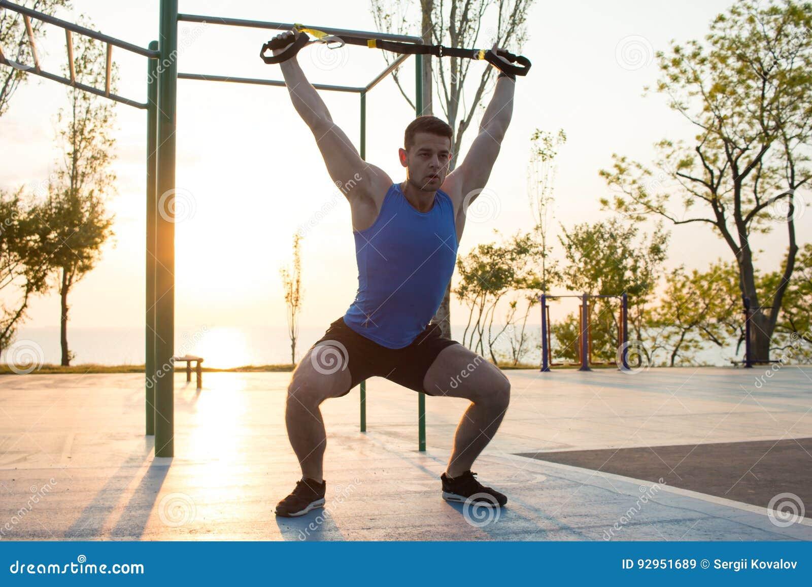 Séance d entraînement avec des courroies de suspension dans le gymnase extérieur, l homme fort s exerçant tôt dans le matin sur l
