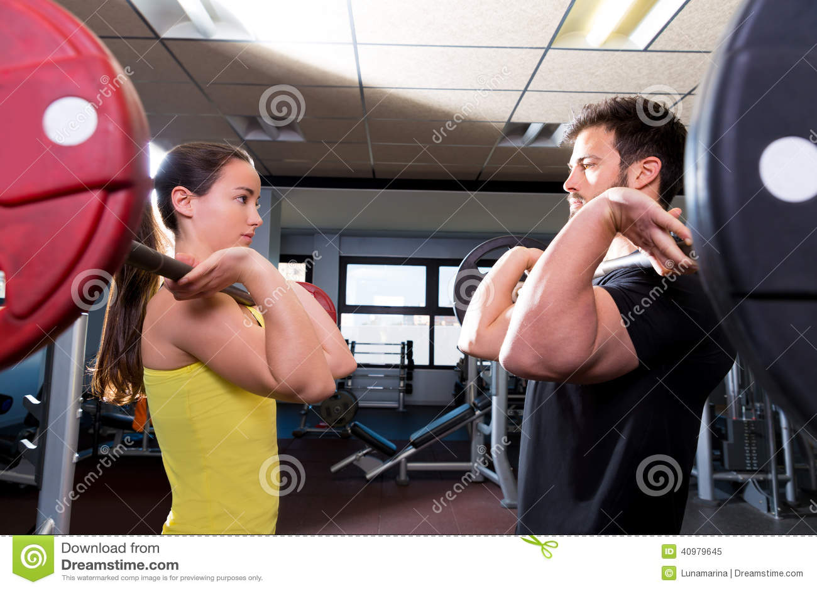 Séance d entraînement d homme et de femme de Barbell au gymnase de forme physique