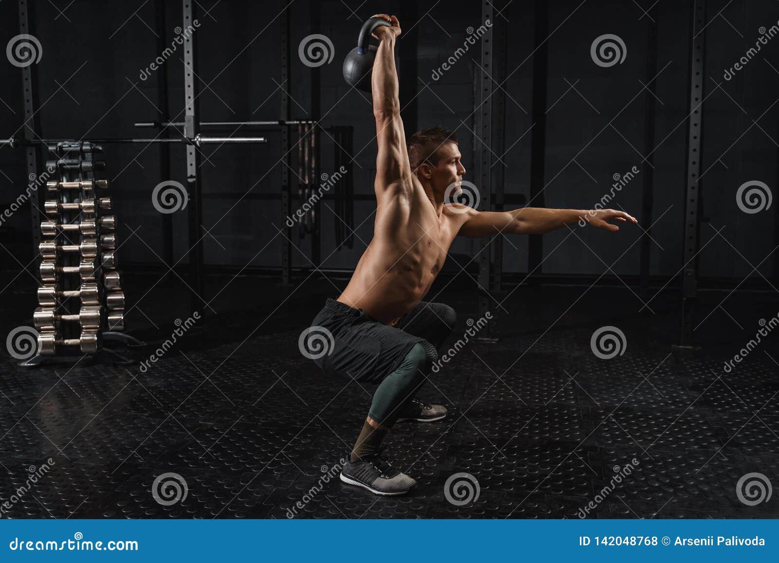 Séance d entraînement d homme d exercice d oscillation de Kettlebells au gymnase Formation de CrossFit