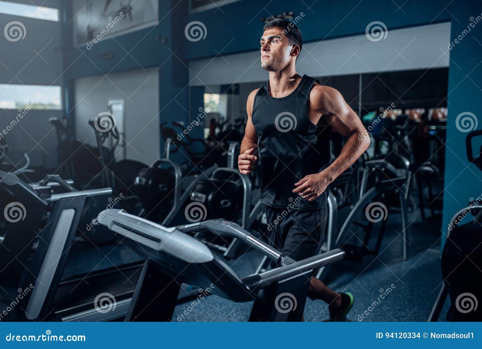 Séance d entraînement masculine d athlète sur la machine courante d exercice
