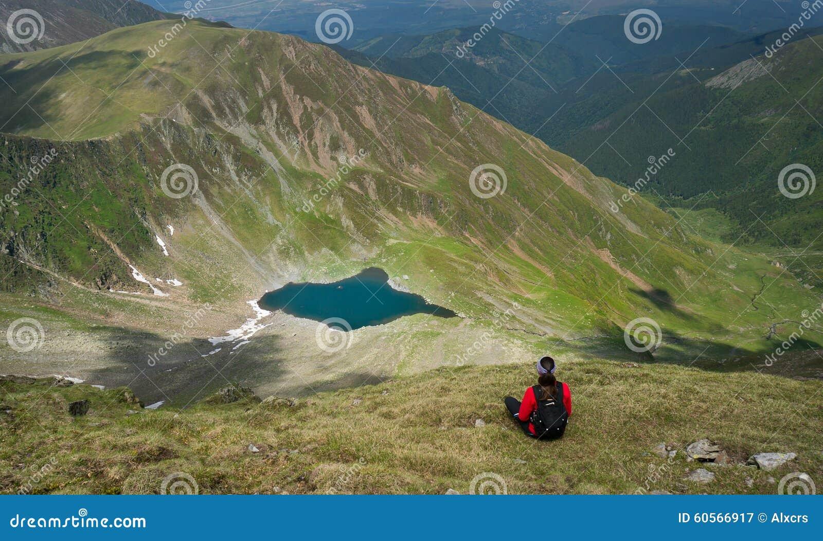 Séance de jeune femme et admirer un beau lac dans les montagnes
