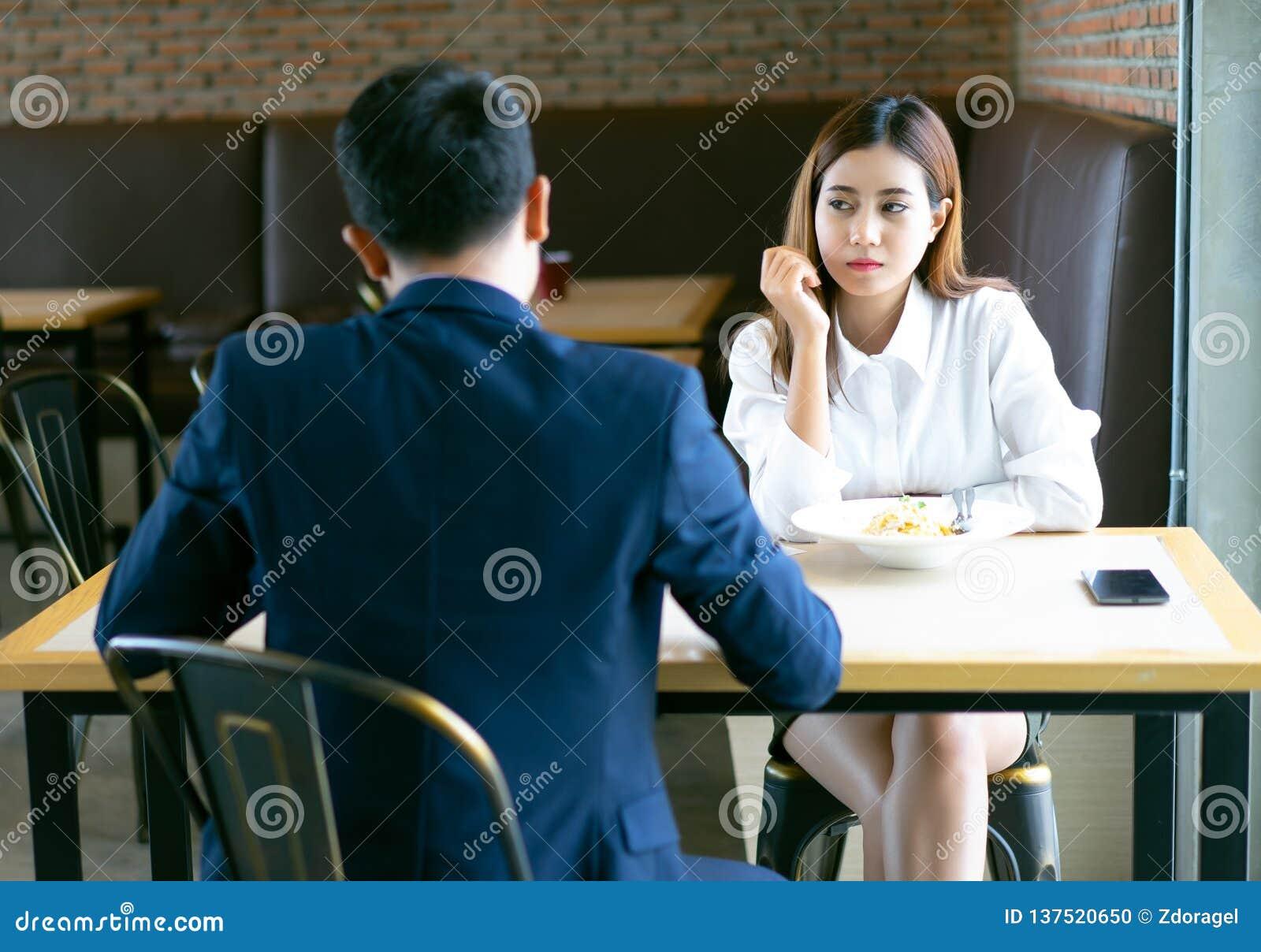 Séance et déjeuner asiatiques ennuyés fatigués de fille avec son ami à un café et au regard loin Les jeunes couples émotifs obtie