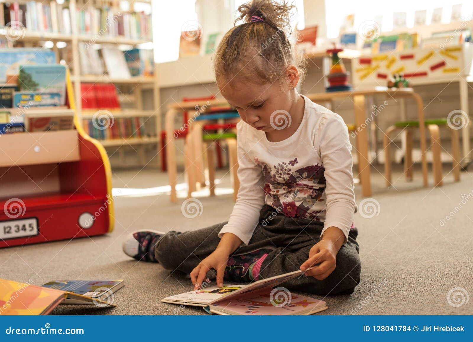 Séance et lecture de petite fille d élève du cours préparatoire un livre dans la bibliothèque Enfant avec des livres près d une b