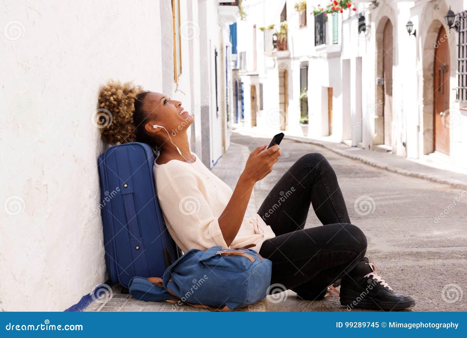 Séance femelle de voyageur d afro-américain sur le trottoir et musique de écoute de téléphone intelligent
