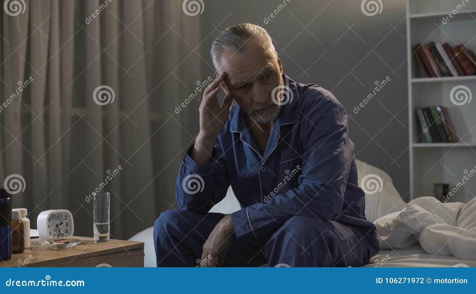 Séance masculine supérieure dans le lit et douleur de mal de tête terrible la nuit