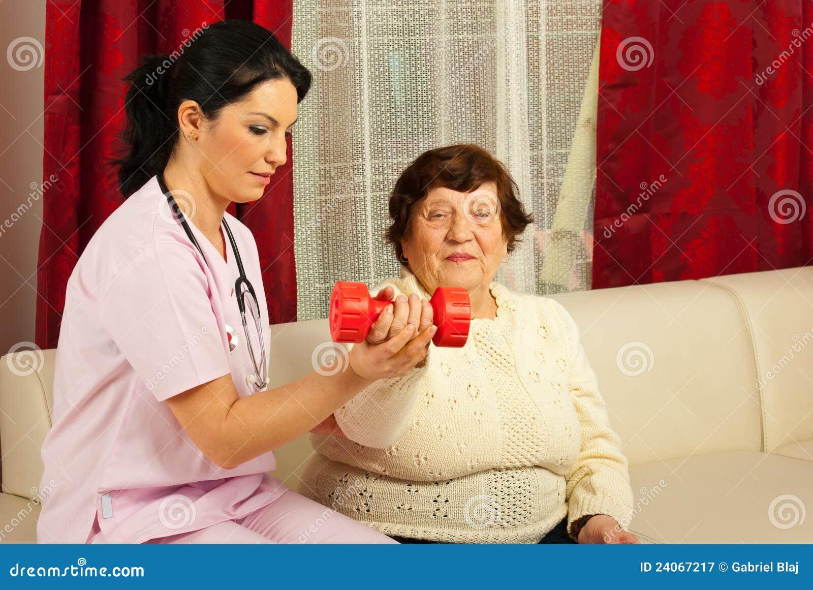 Sénior de ajuda do terapeuta para fazer exercícios