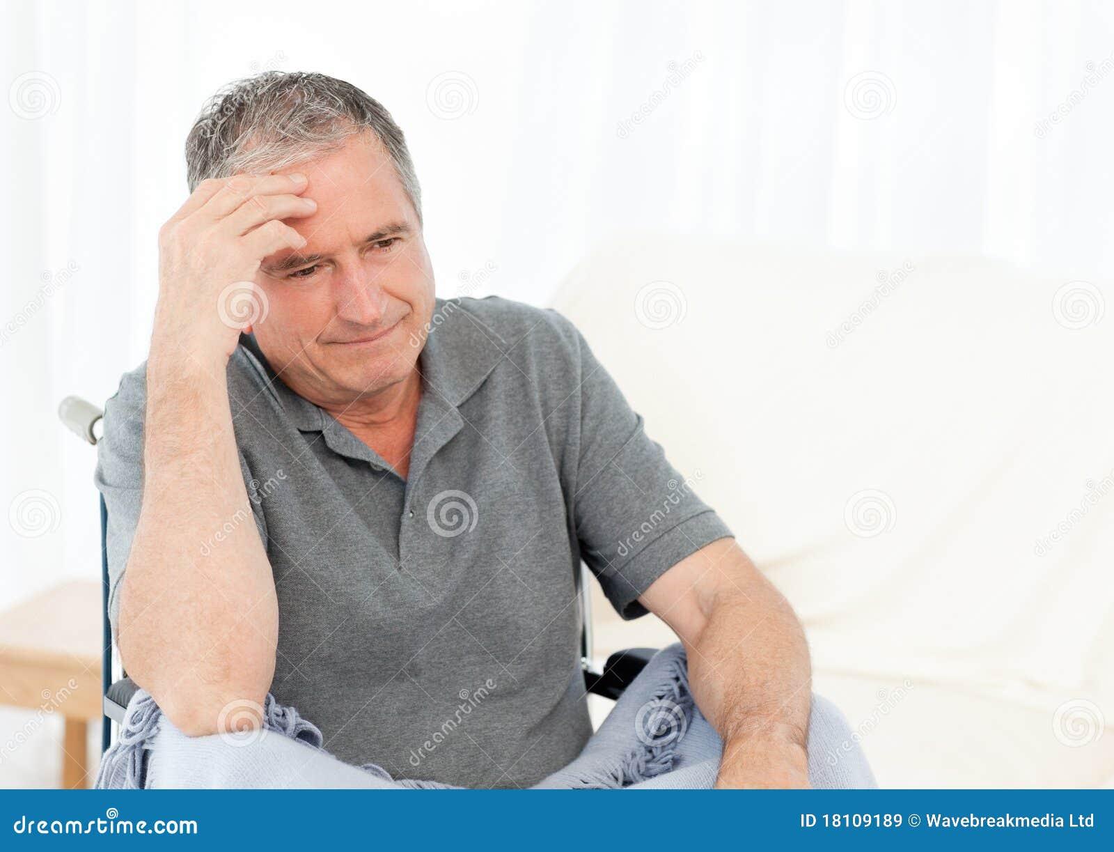 Sénior em sua cadeira de rodas que tem uma dor de cabeça