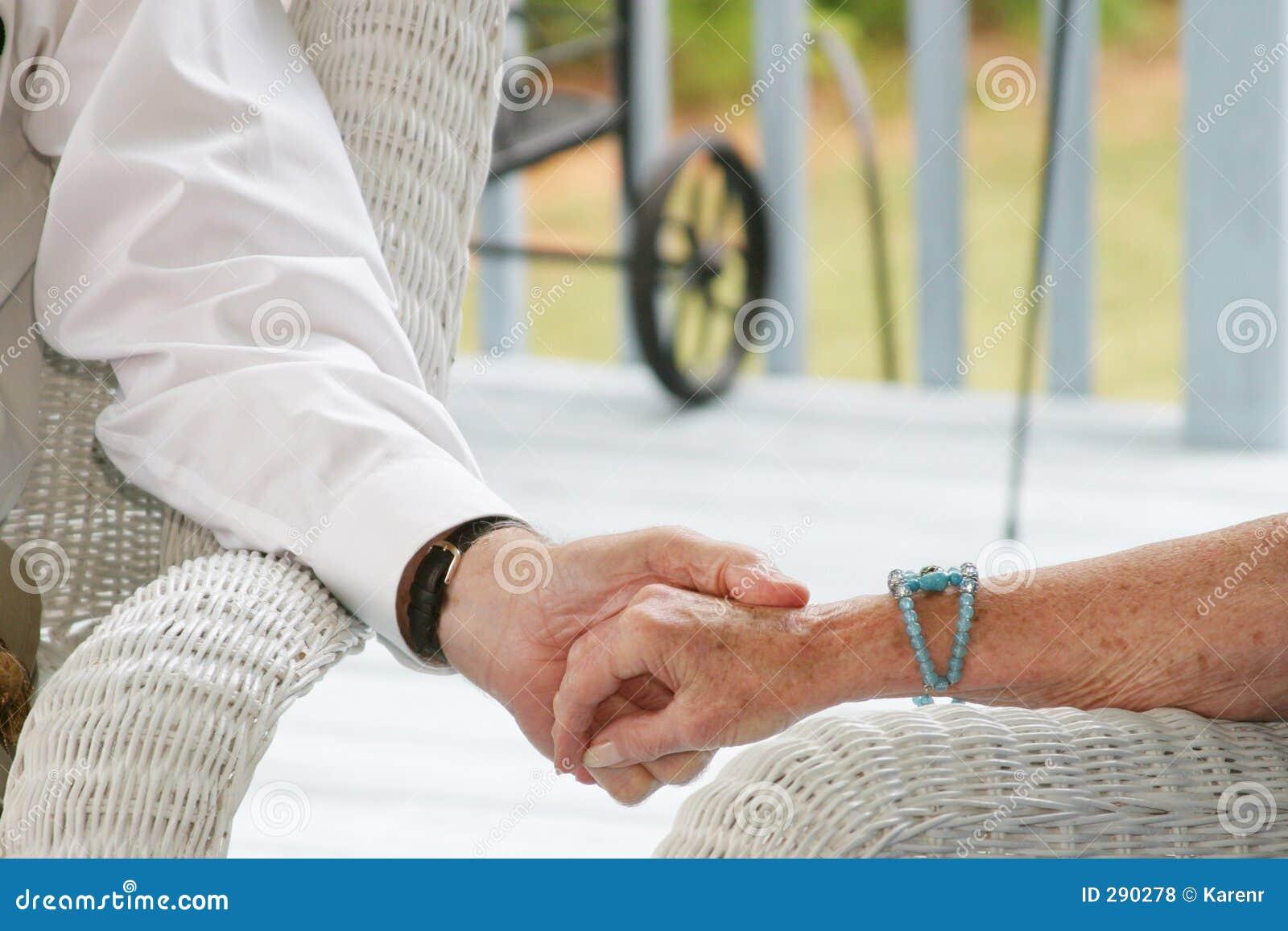 Séniores que prendem as mãos