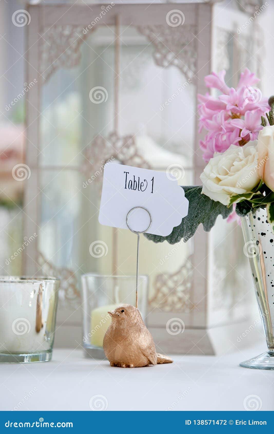 Série da decoração da tabela do casamento - ramalhete do rosa e o branco das flores e um pássaro que guarda um sinal da tabela 1