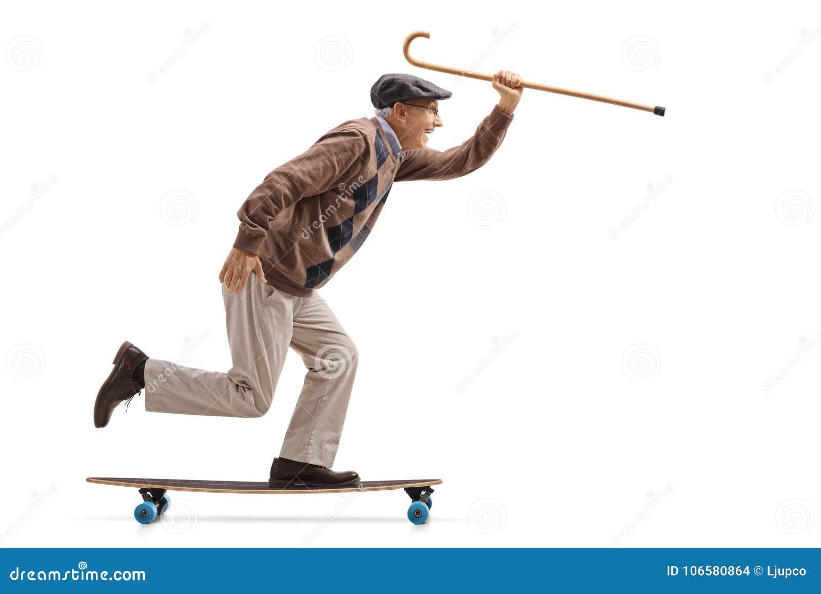 Sênior alegre que guarda um bastão e que monta um longboard