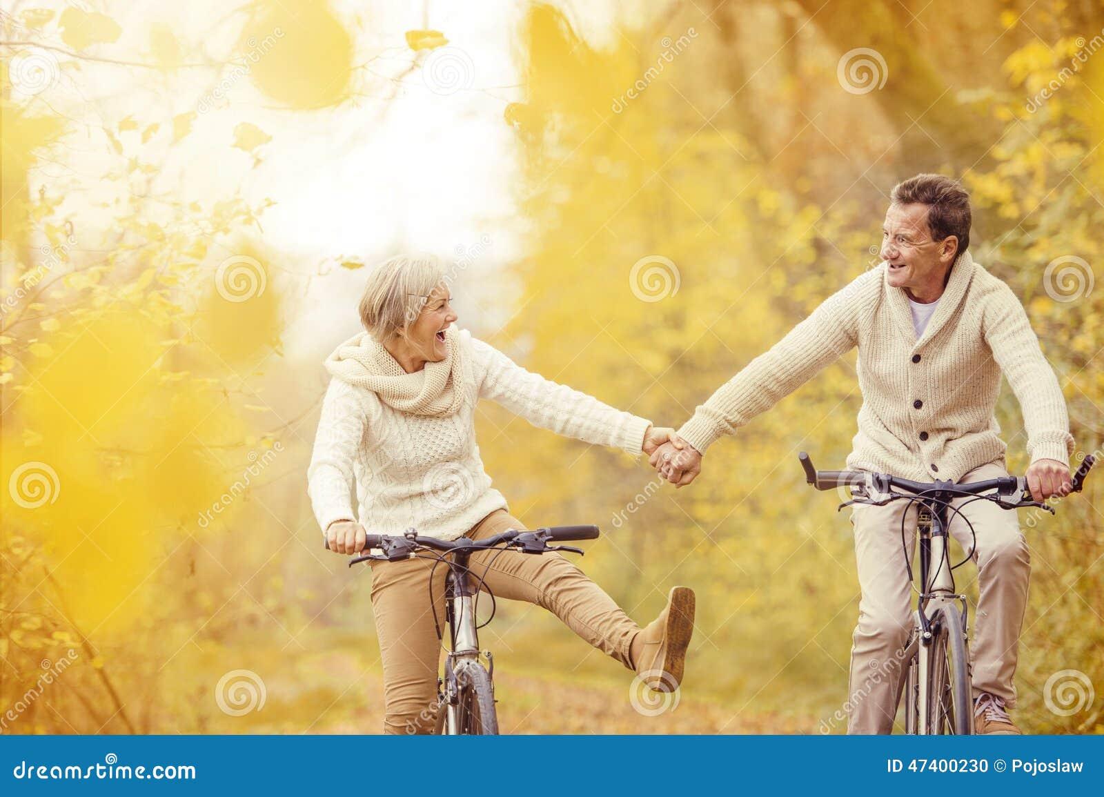 Sêniores ativos que montam a bicicleta