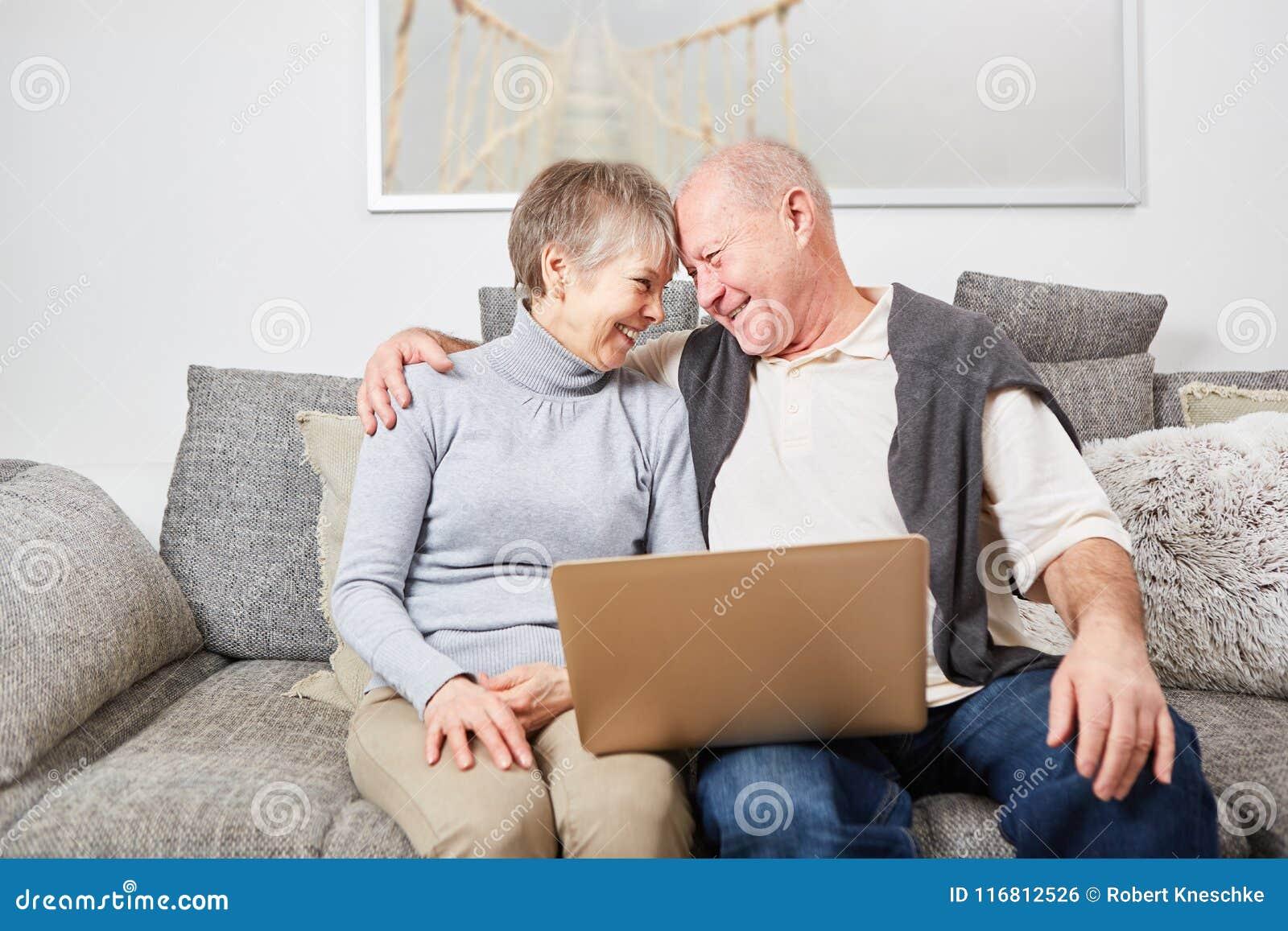 Sêniores no abraço do amor no sofá