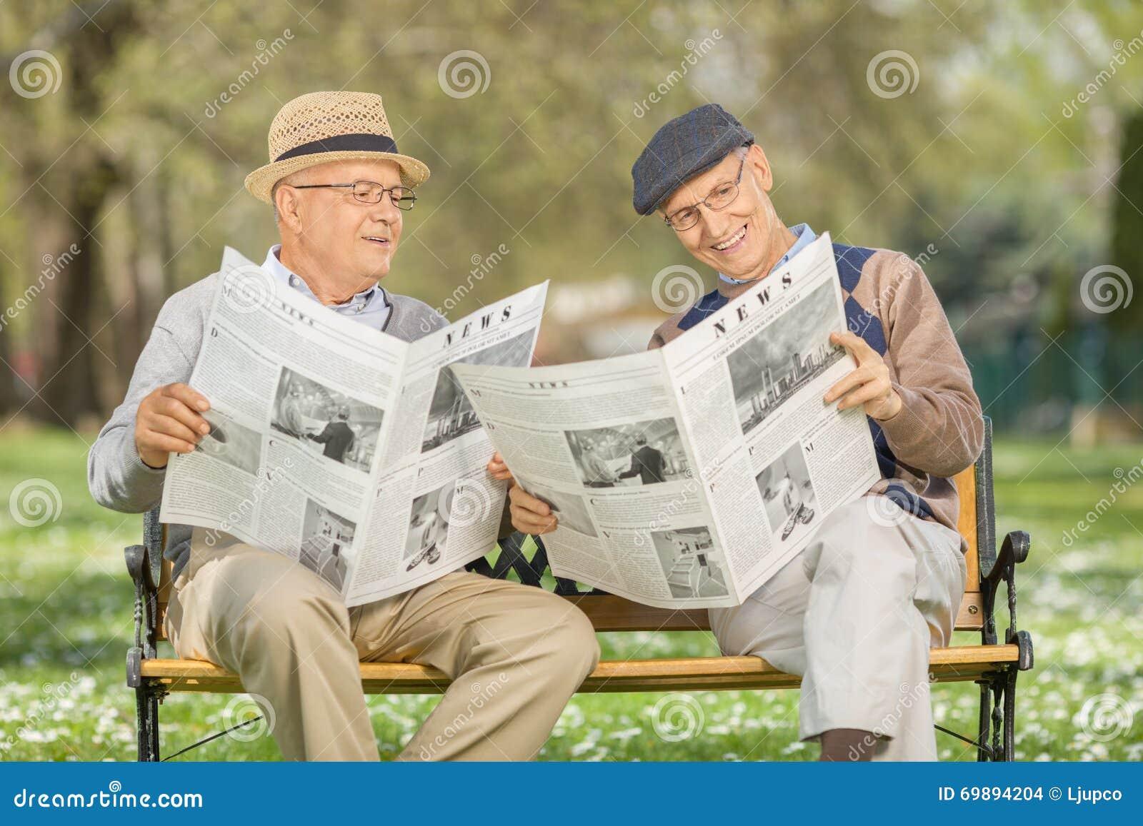 Sêniores que leem o jornal em um parque