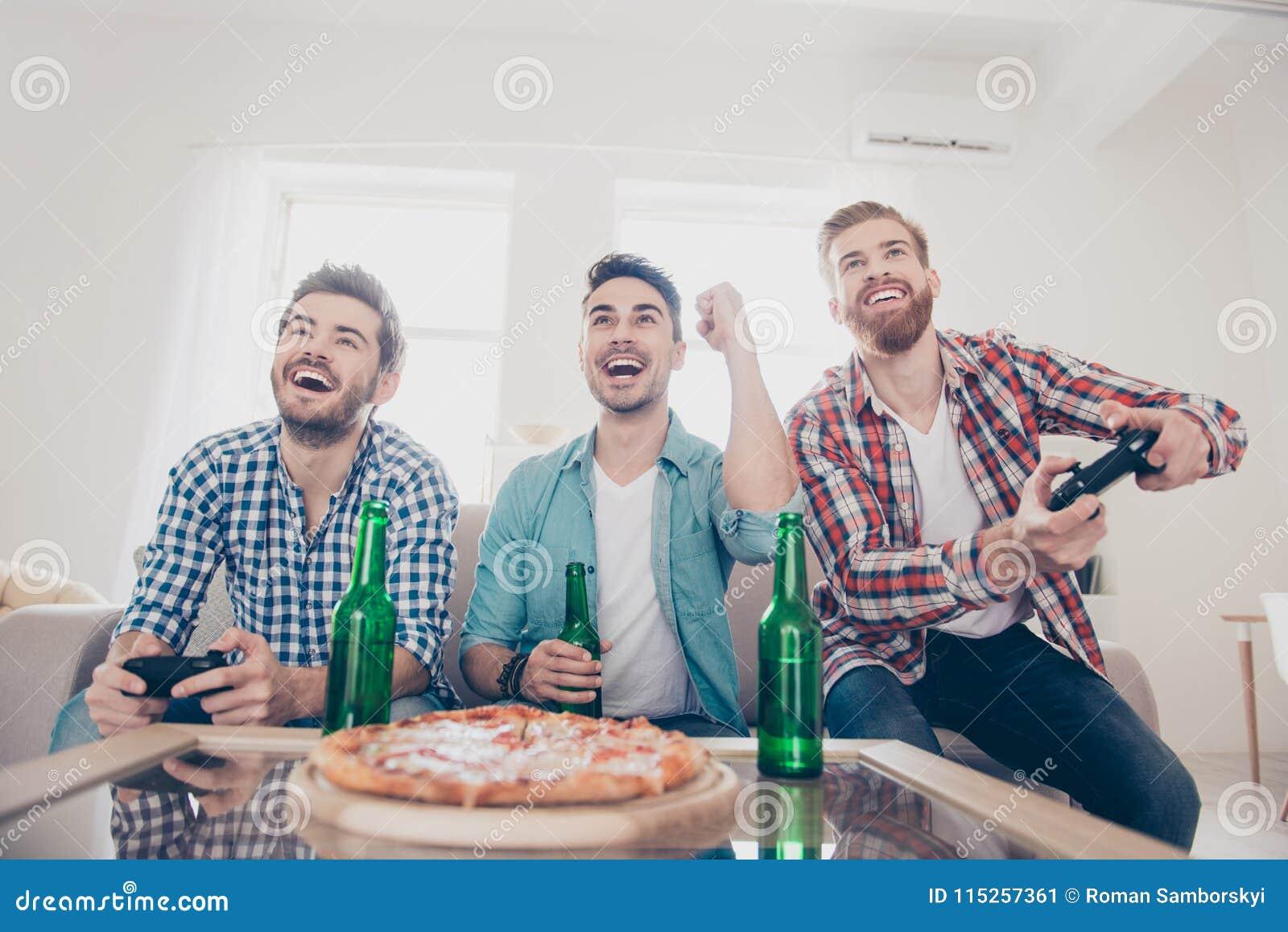 Sì! Gruppo dei vincitori! Vita del ` s degli uomini del celibe Un angolo basso di tre uomini allegri felici, sedentesi sul sofà e