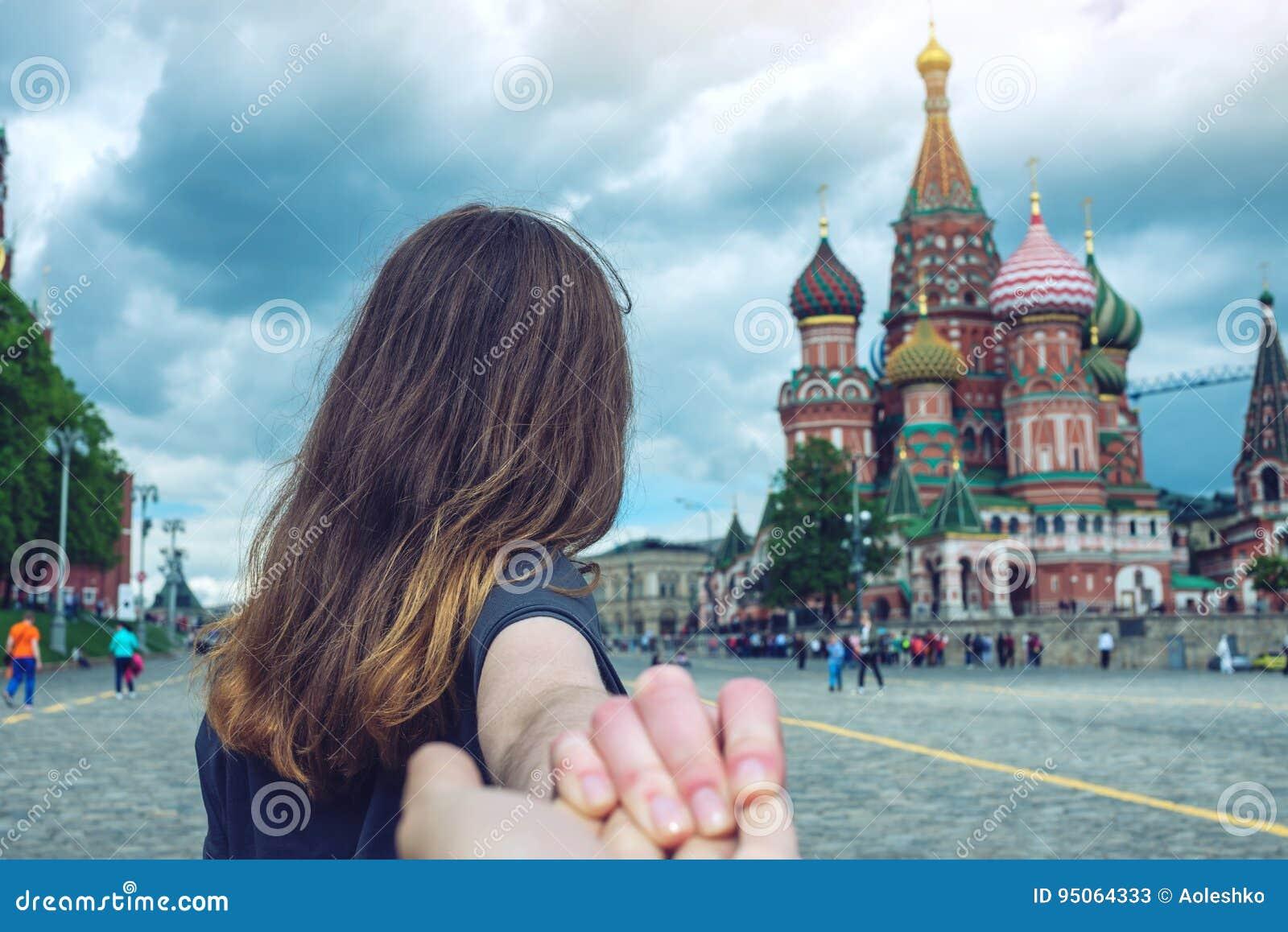 Sígame, muchacha morena que lleva a cabo la mano lleva al cuadrado rojo en Moscú Rusia