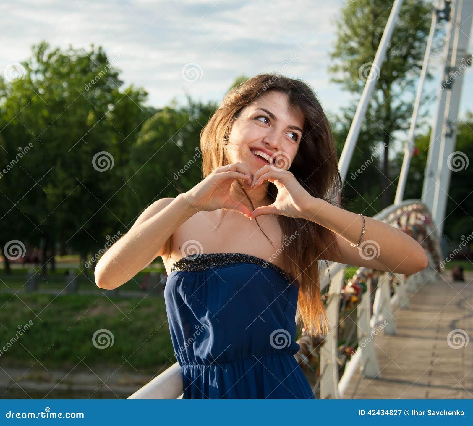 Símbolo agradable alegre de la demostración de la muchacha del corazón