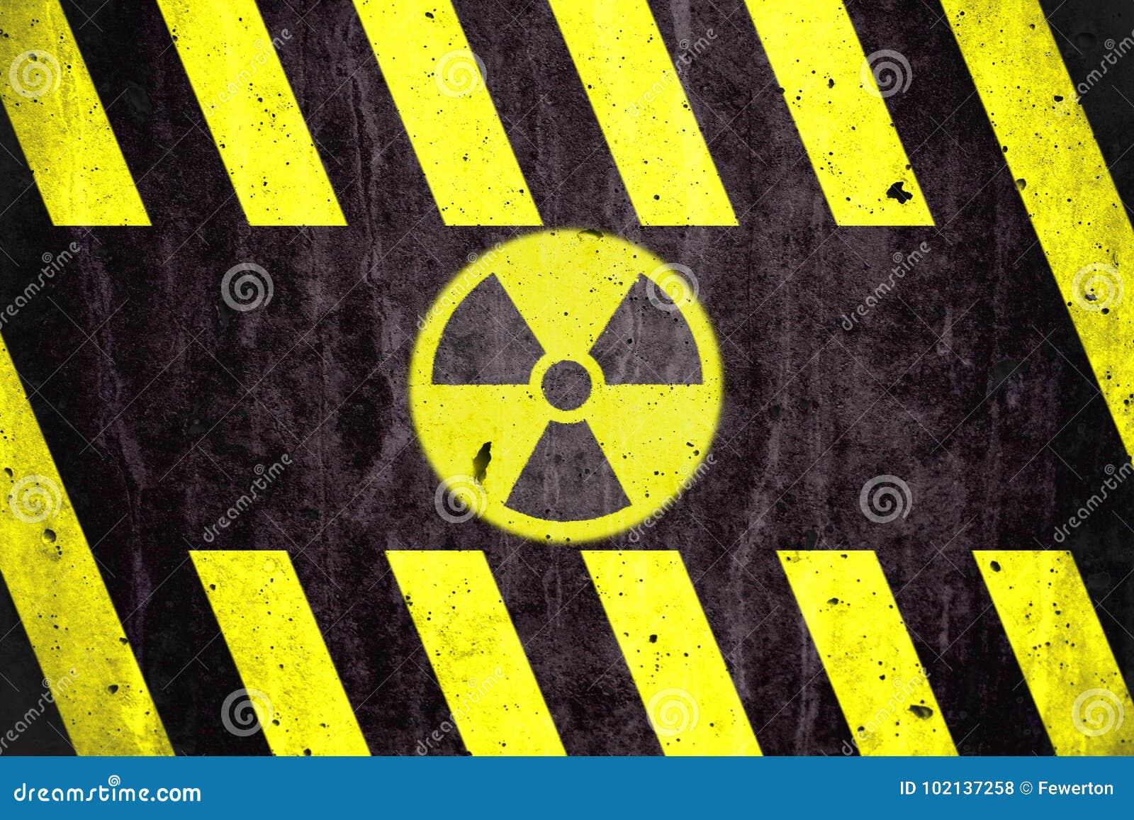 Símbolo radiactivo del peligro de la radiación ionizante con amarillo y rayas negras pintadas en un muro de cemento masivo