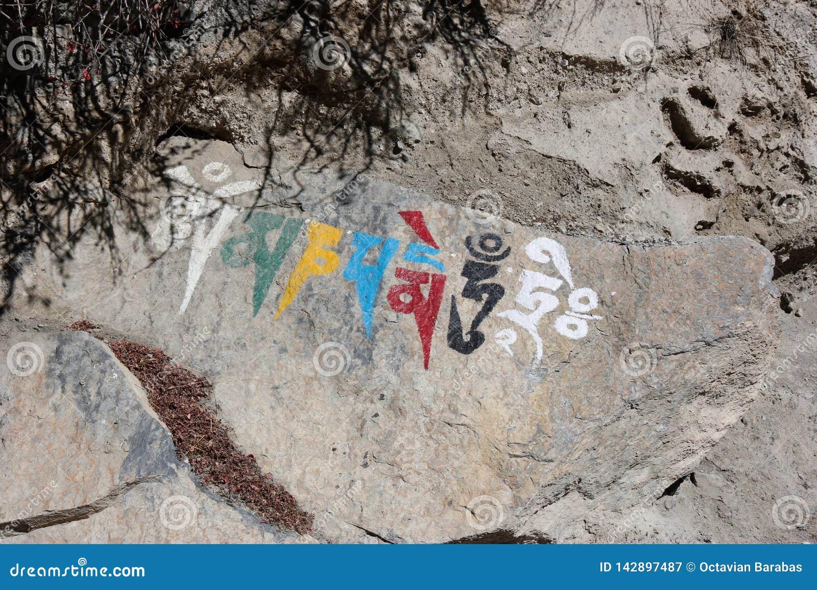 Símbolo religioso nepalês que escreve em uma rocha