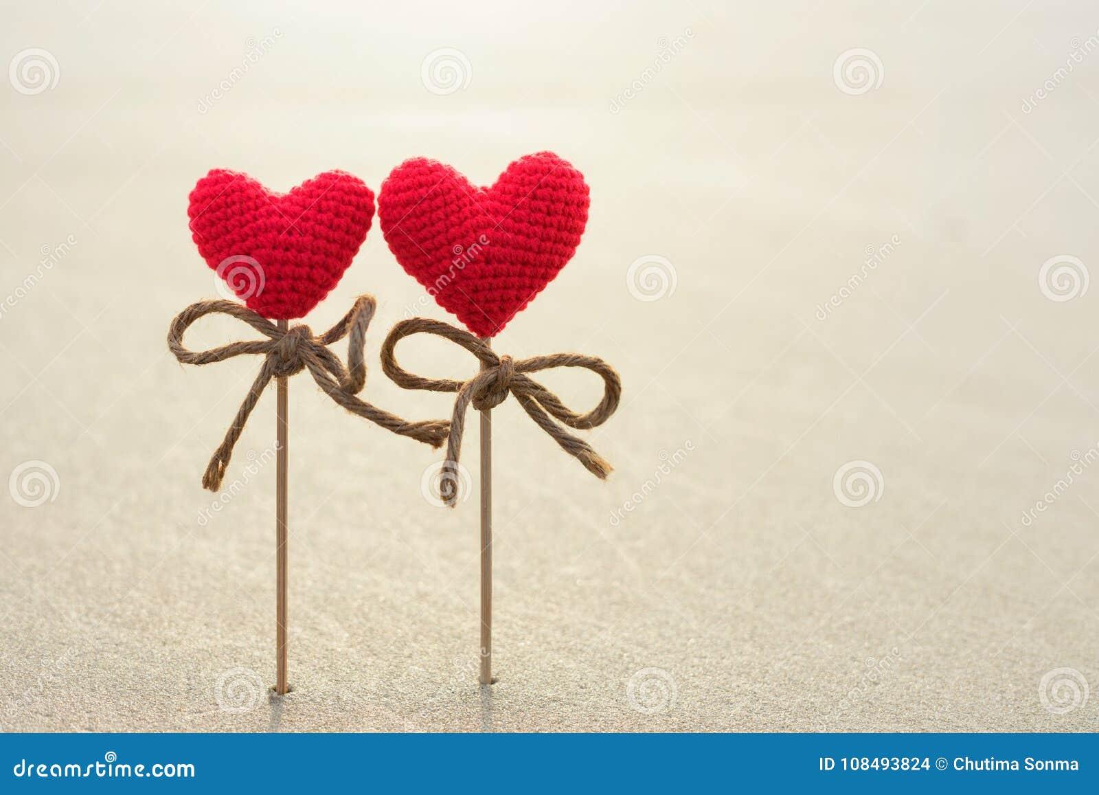 Símbolo romántico de dos corazones rojos en la superficie de la arena,