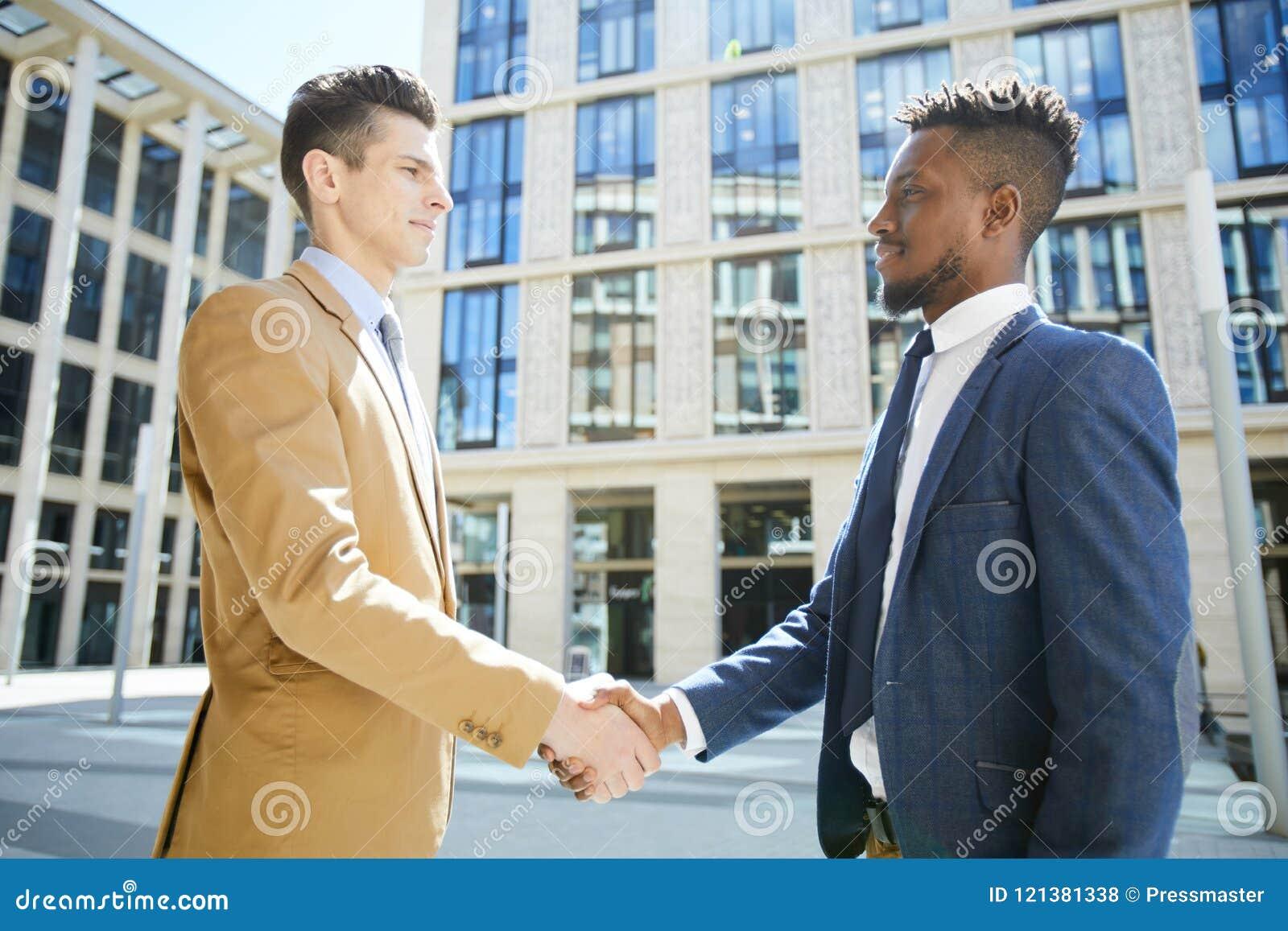 Sócios comerciais que agitam as mãos no distrito financeiro