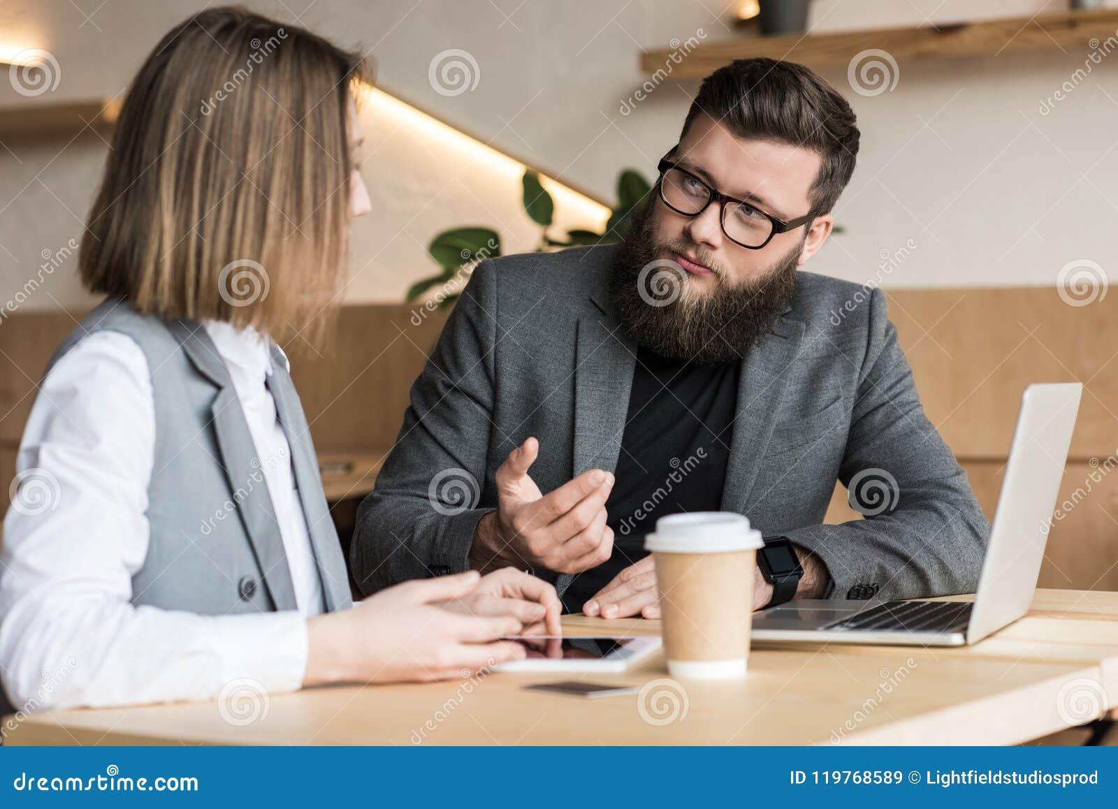 Sócios comerciais que têm a conversação no café moderno com dispositivos e café