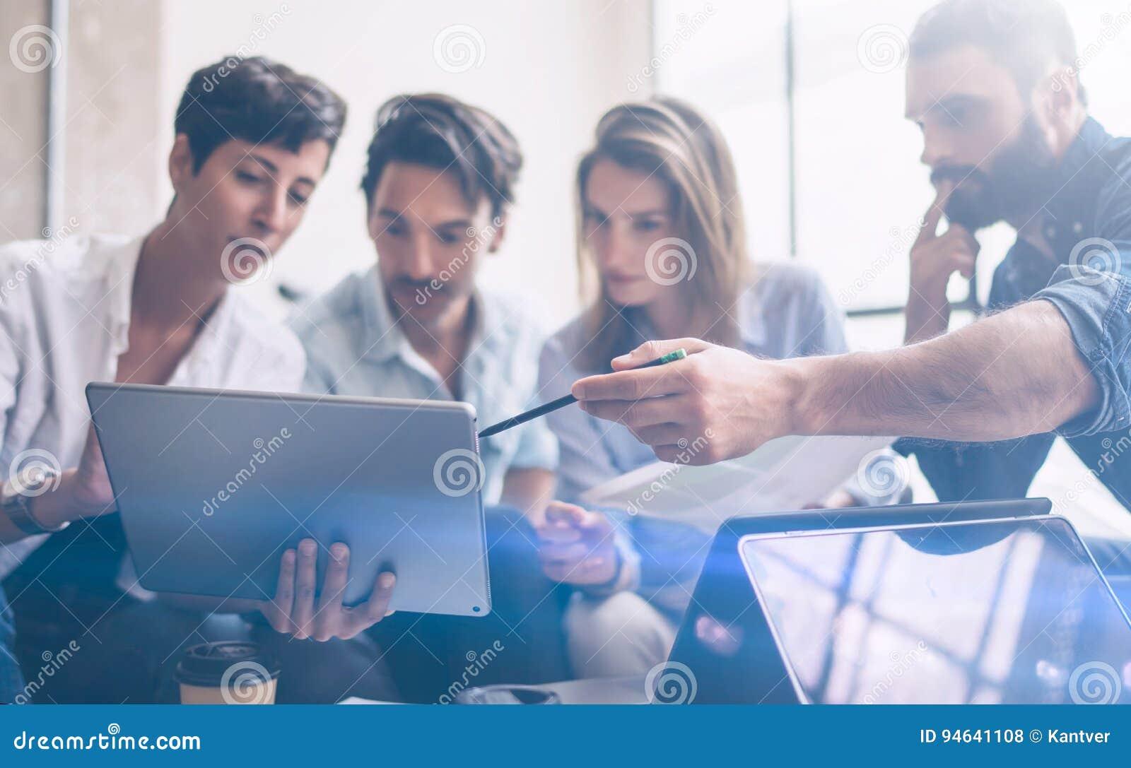 Sócios novos que fazem a pesquisa para o sentido novo do negócio Homem de negócios novo que trabalha o portátil moderno e que mos