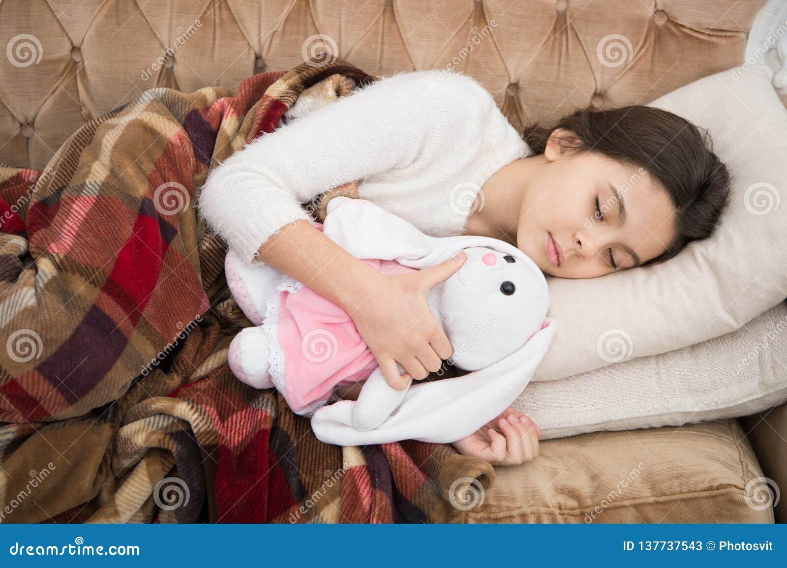 Sömn med leksaken Flickan tycker om aftontid med den favorit- leksaken Ungen lägger bakgrund för filten för kudden för soffan för