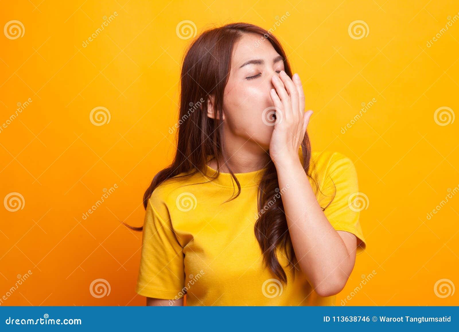 Sömnig ung asiatisk kvinnagäspning