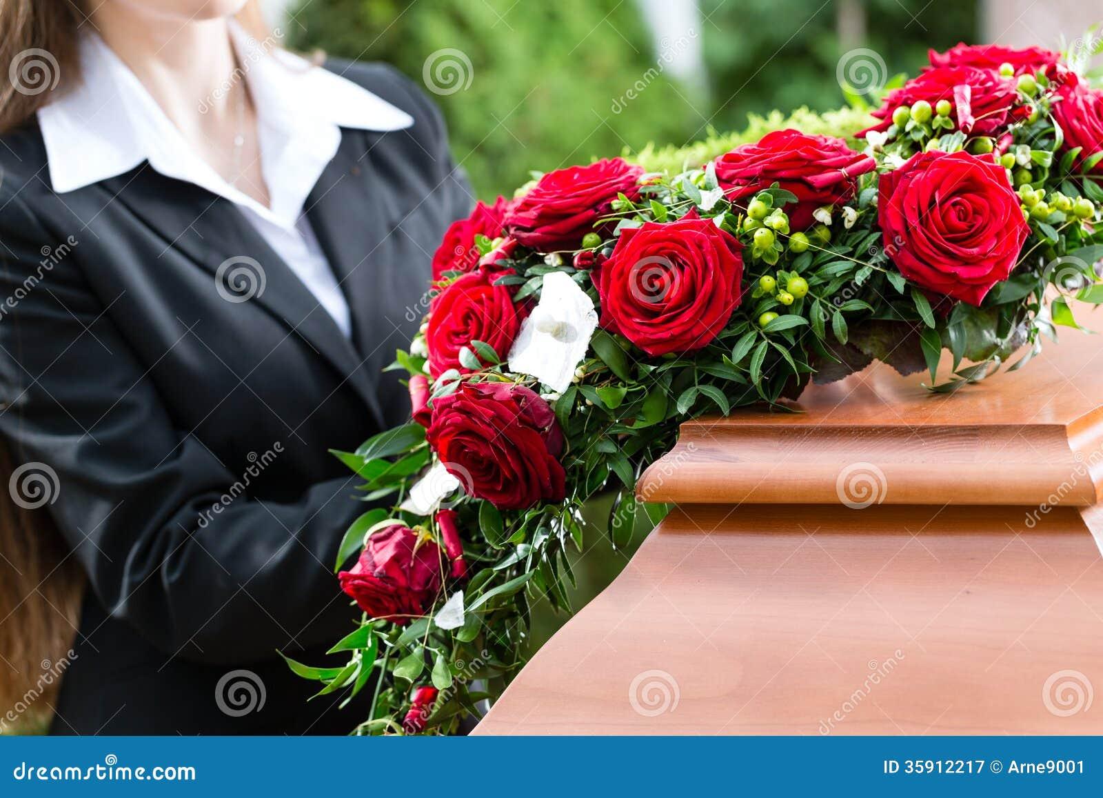 Sörjande kvinna på begravningen med kistan