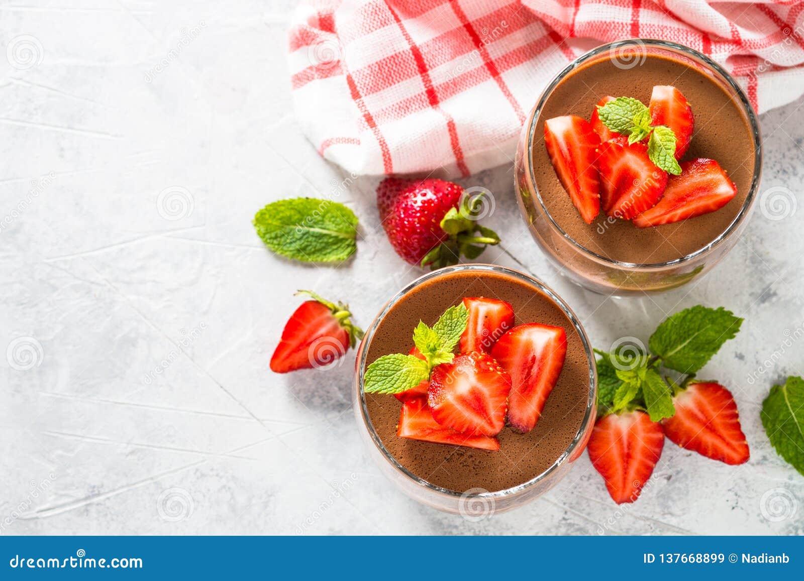 Söt efterrätt för chokladpannacotta med jordgubbar i exponeringsglas