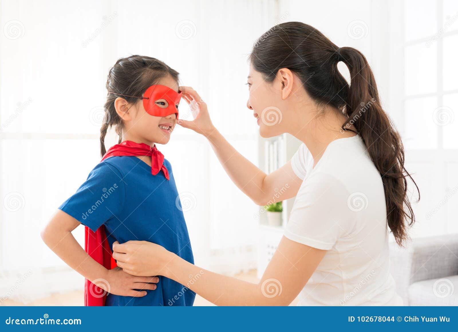 Söt flickaunge som bär röd kappalek som superhero