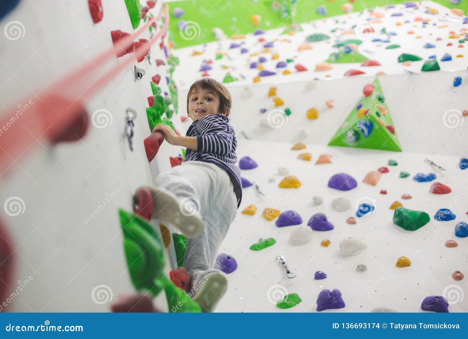 Söt liten förskole- pojke som inomhus klättrar väggen