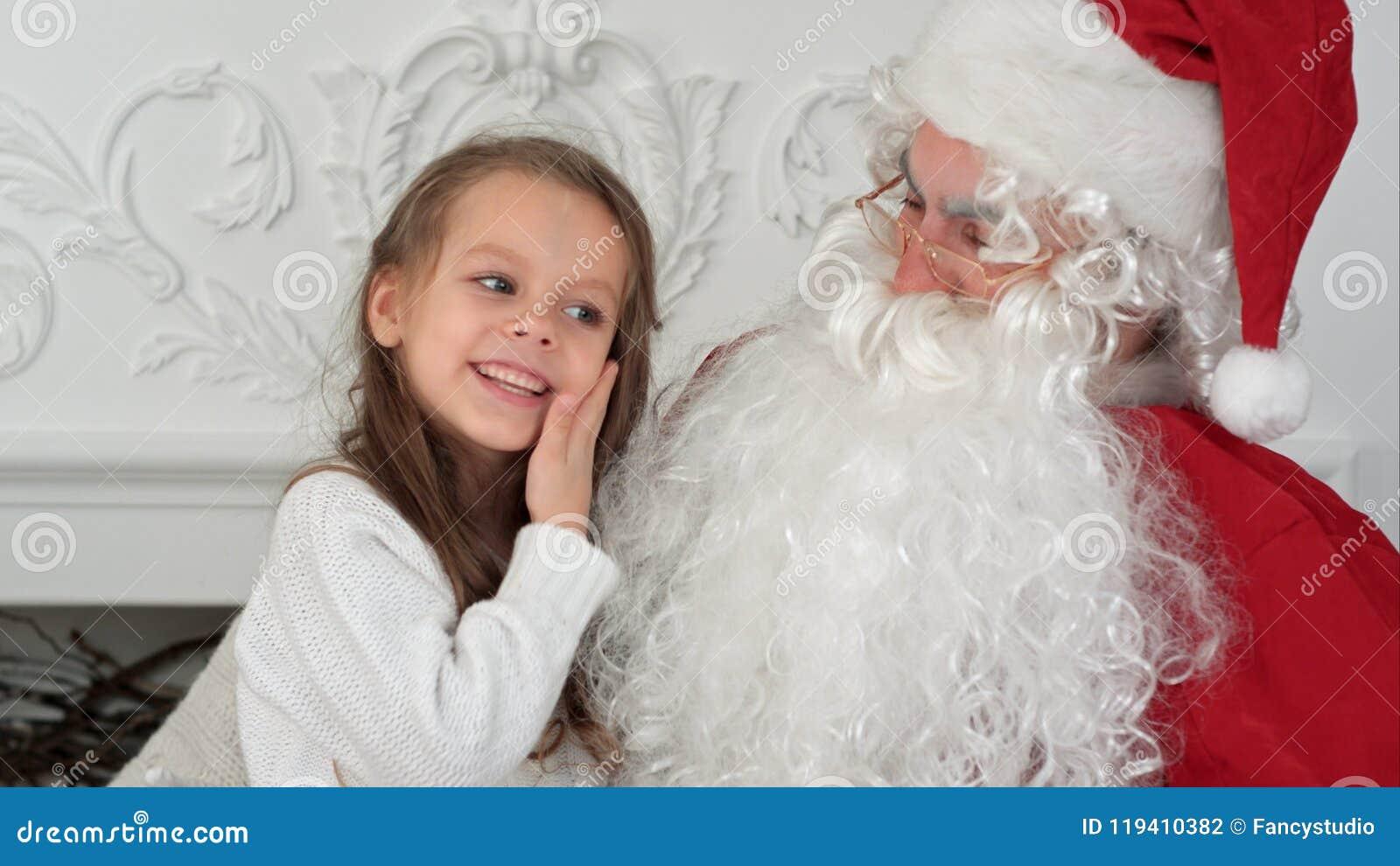 Söt liten flicka på den Santa Claus varven som berättar honom vad hon önskar för jul