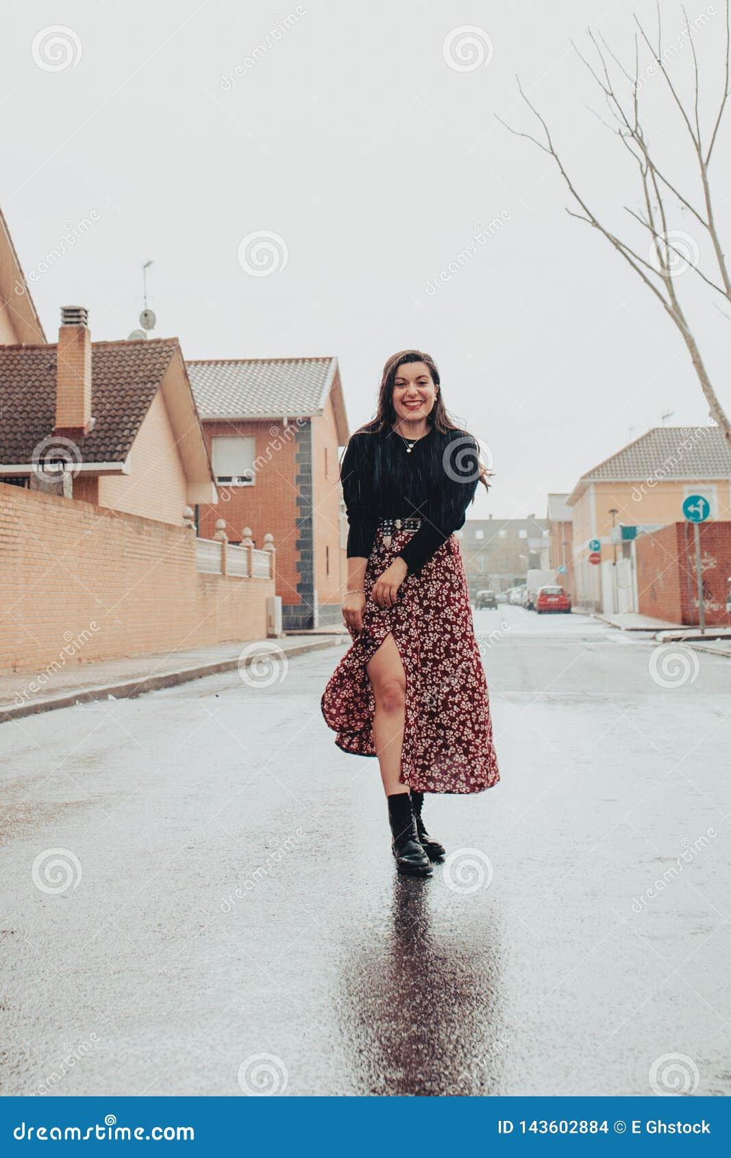 Söt trendig ung flicka som ler i regnet