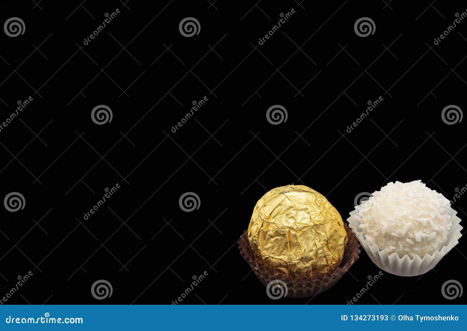 Söt vit kräm för godis med kokosnötisolaten på en guld- mutter för svart bakgrund
