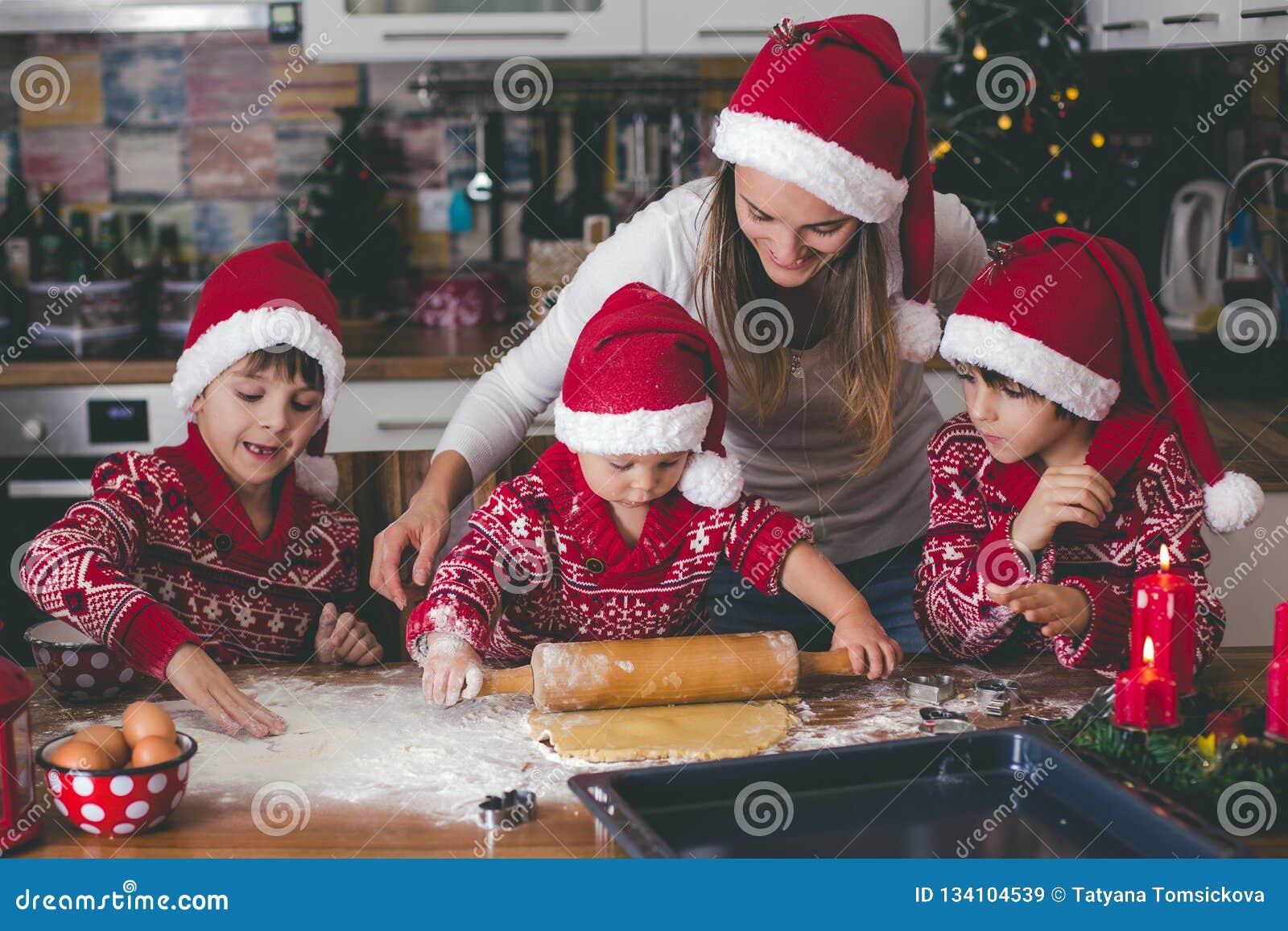 Sött litet barnbarn och hans äldre broder, pojkar, hjälpande mamma som hemma förbereder julkakor