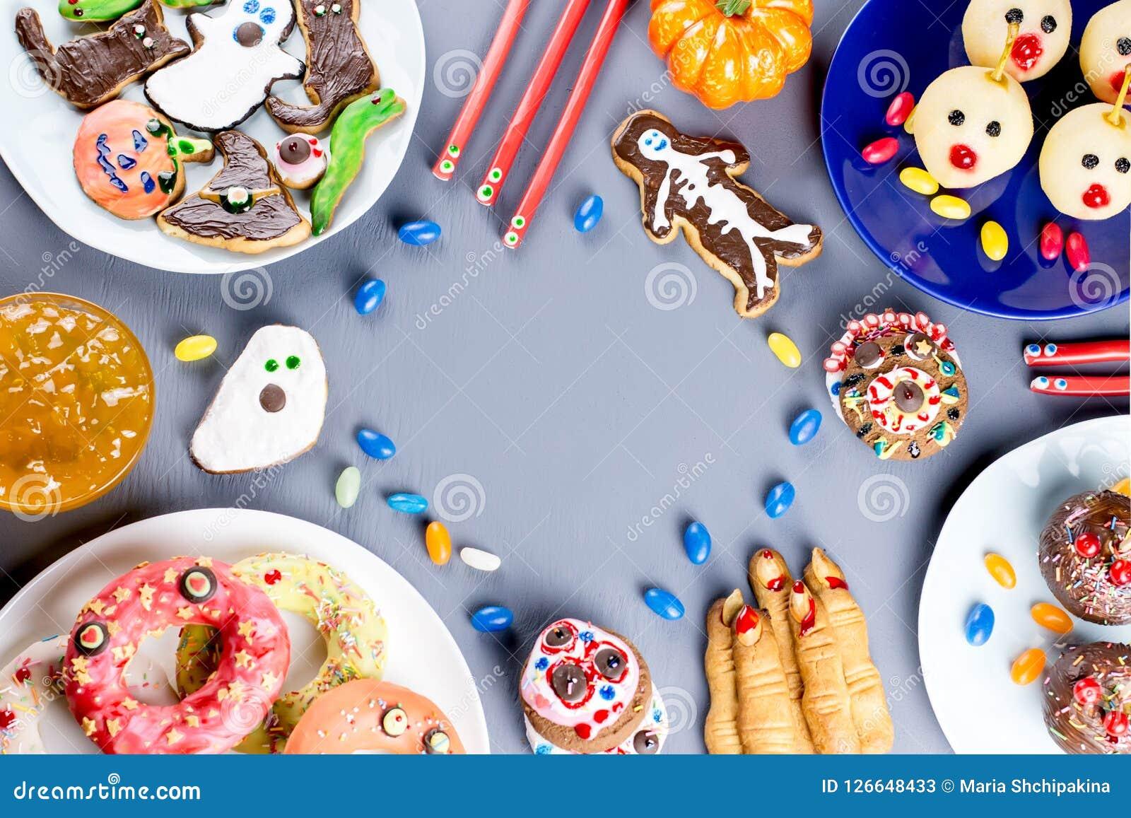Süße Festlichkeiten Halloweens, Parteilebensmittelkonzept Furchtsame Plätzchen, Monsterkekse und Früchte auf grauem Hintergrund