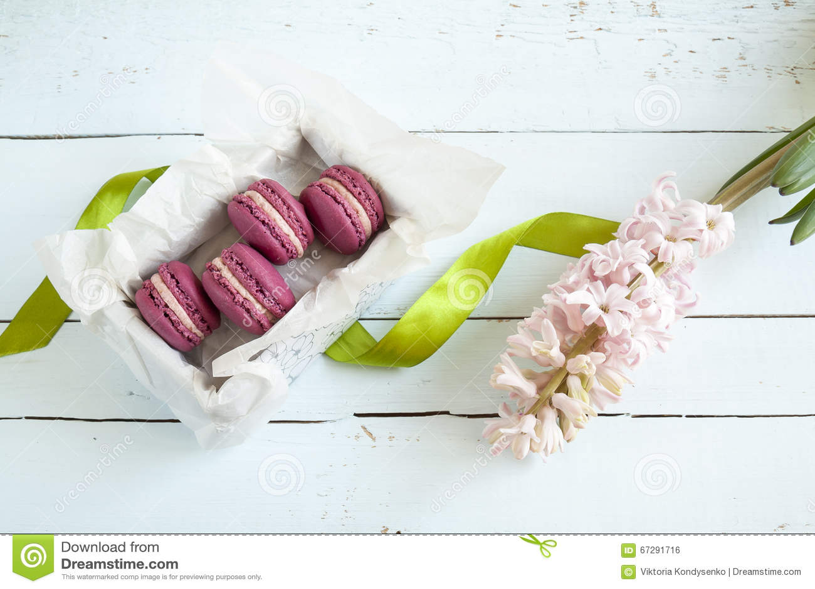 Süße hochrote französische Makronen mit Kasten und Hyazinthe auf Licht färbten hölzernen Hintergrund
