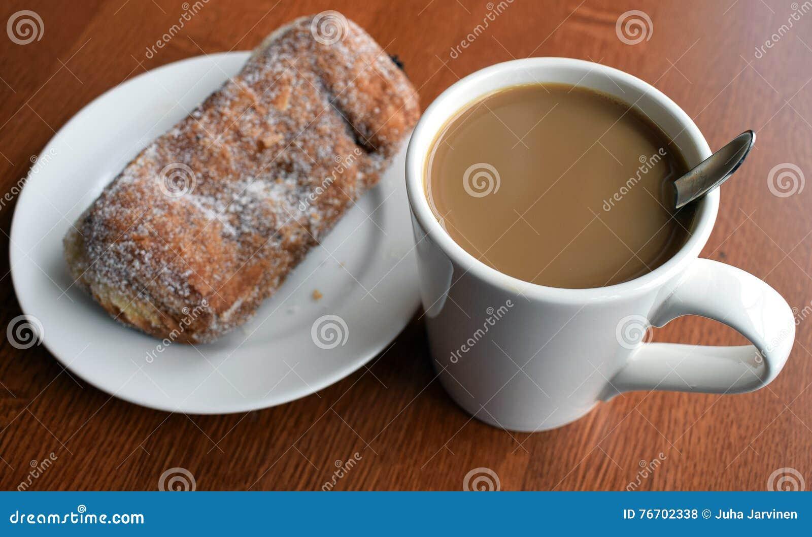Süßes Hörnchen und ein Tasse Kaffee im Hintergrund
