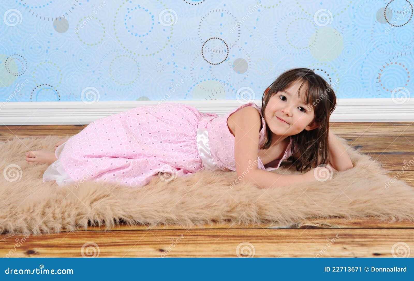 Süßes kleines Mädchen, das playfully auf Pelzwolldecke aufwirft