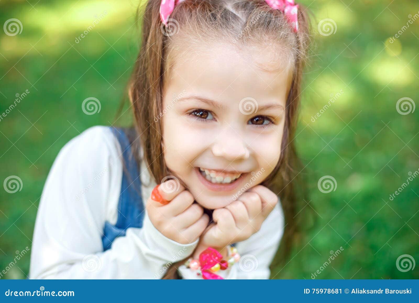 Bilder zu Nettes kleines blondes Mädchen mit langen Schwänzen auf dem Kopf, die bunten Kaugummi klebt.